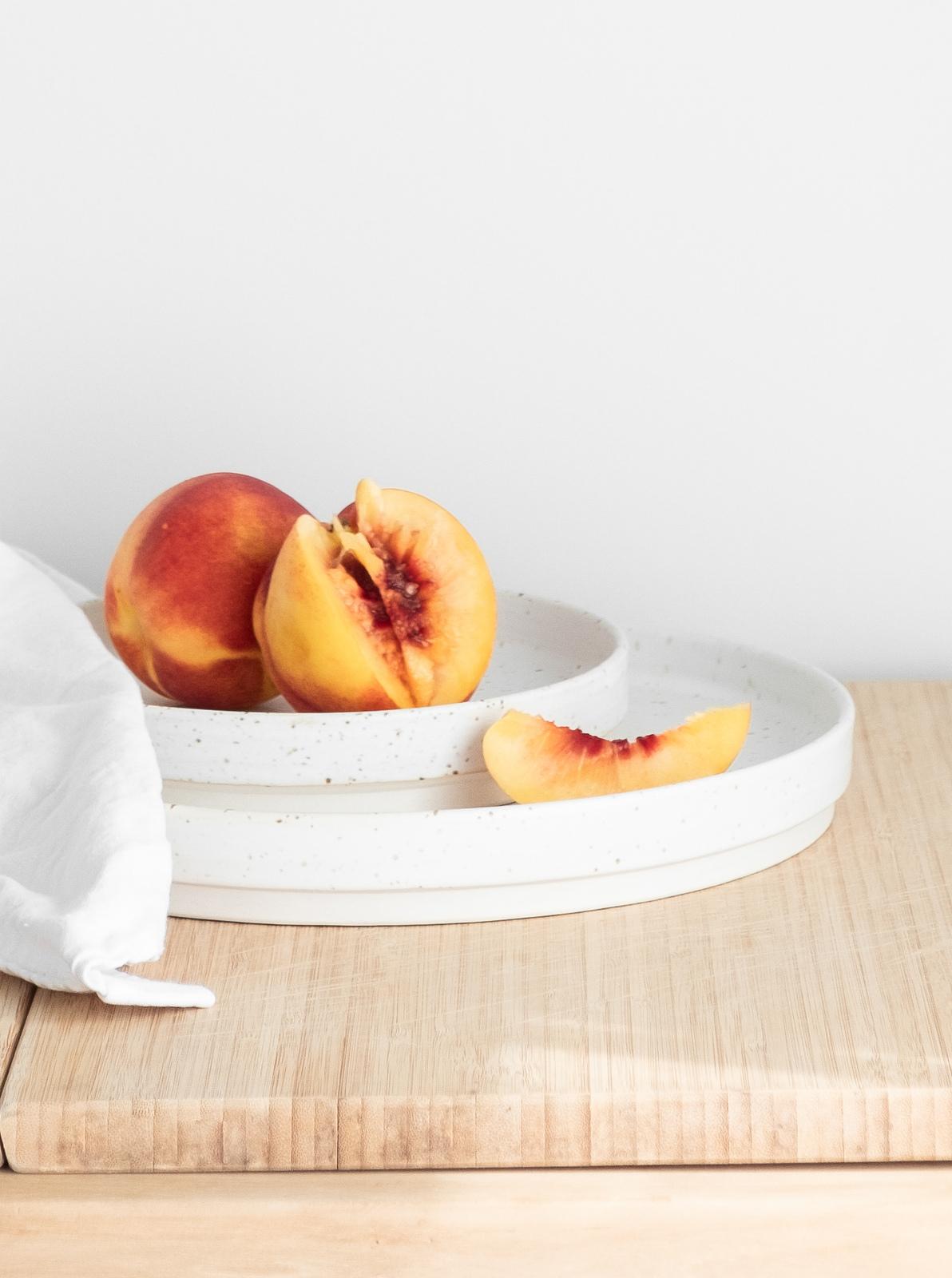 Peach served in beautiful snow ceramic plates