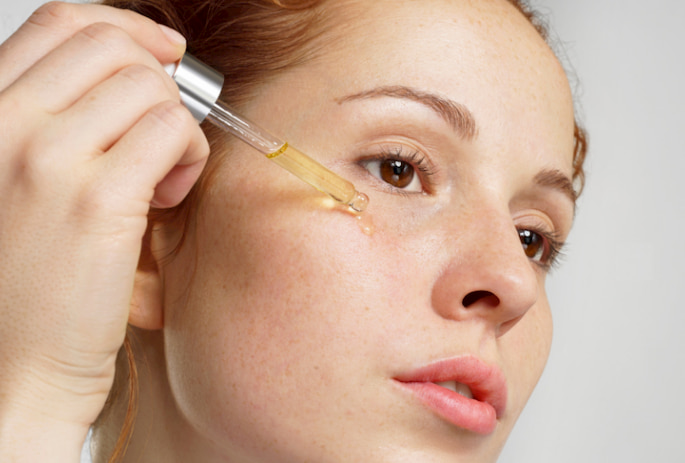 Putting rosehip oil on face