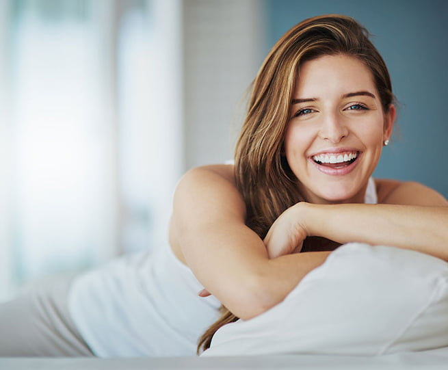 girl with white shirts smiling while laying on her bed