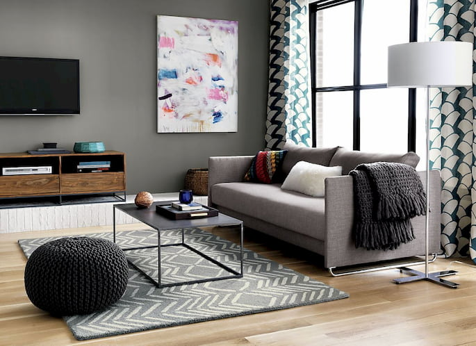 black pouf and grey sofa bed with pillows, table and rug