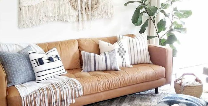 modern leather sofa bed for living room with decorative pillows, with white and gray rug and pouf