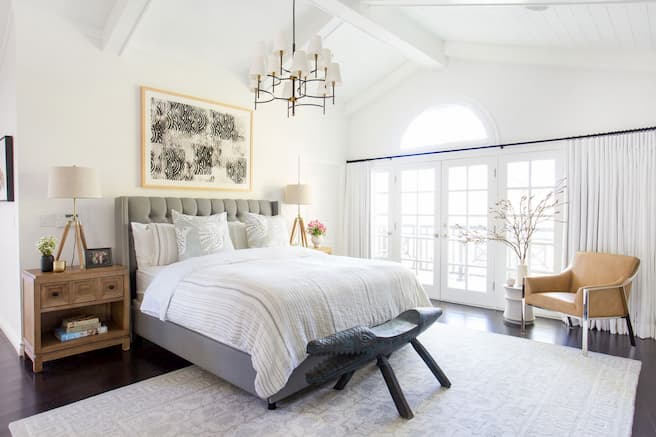 bedroom decor bed with decorative pillows and bedding armchair and side table with books and lamp