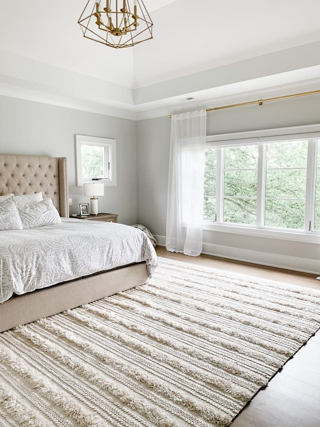 lovely bedroom with beige bed and bedding set with leaves