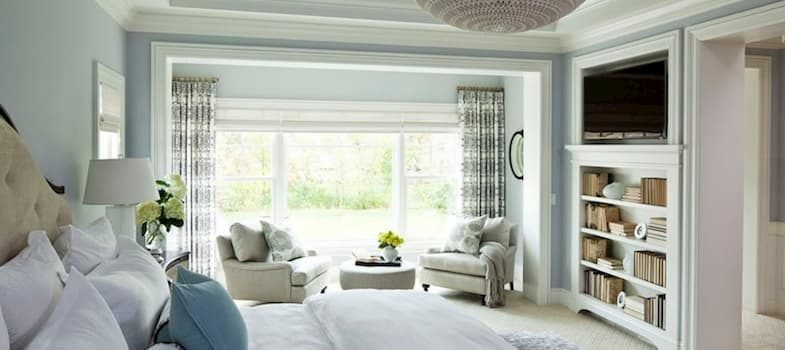 modern bedroom with cirtains bedding and two armchairs one coffee table and shelves with books