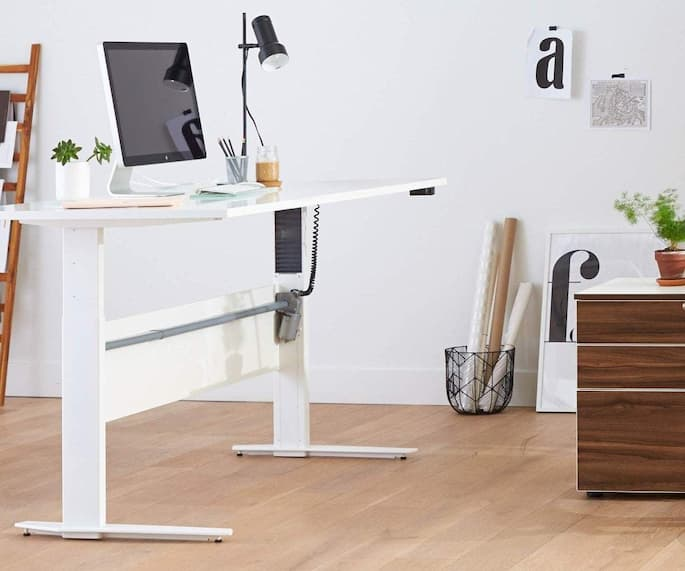 white standing desk with laptop book flower and pens