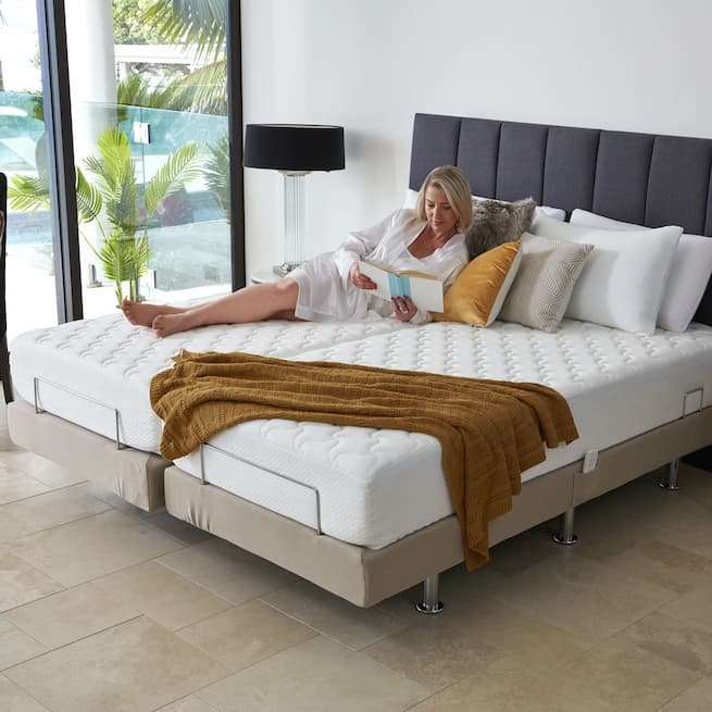 a woman reading a book on an adjustable bed