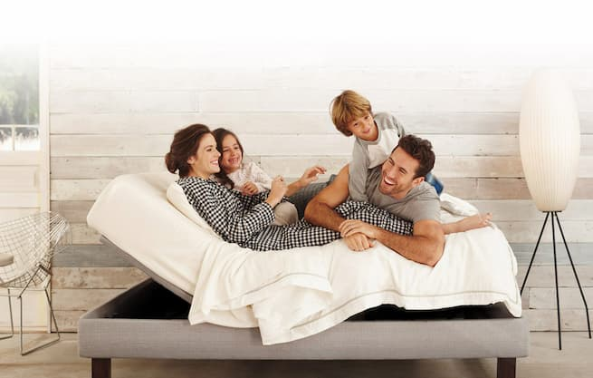 family laying on an adjustable bed