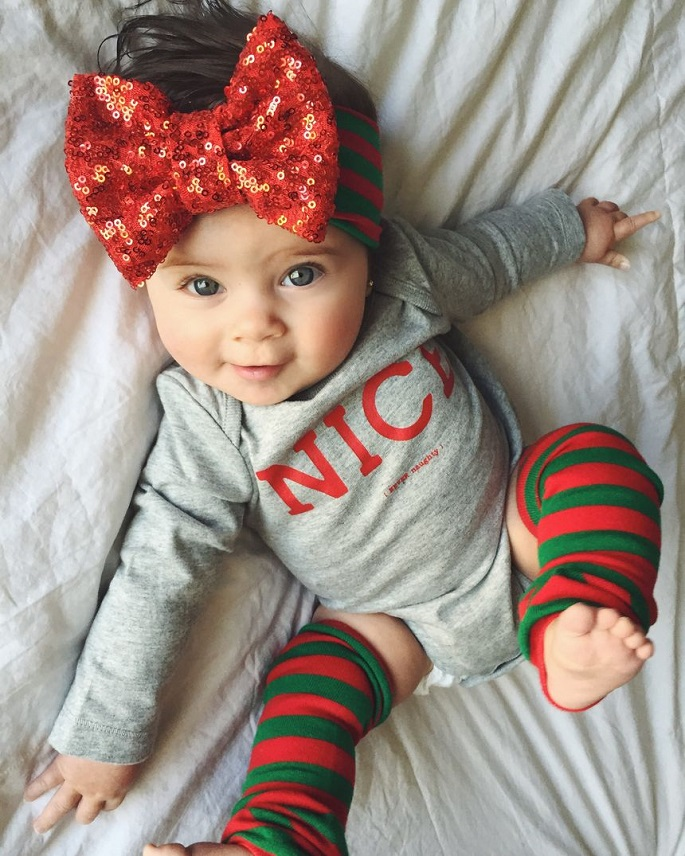 picture of baby wearing gray onesies, bow on the head and red and green socks