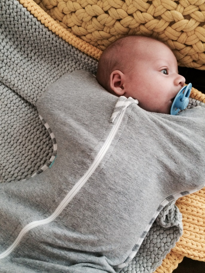 picture of a baby wearing gray swaddle and sleepwear with zipper