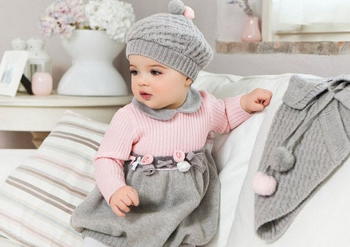 picture of a baby in cute gray and pink outwear on the sofa