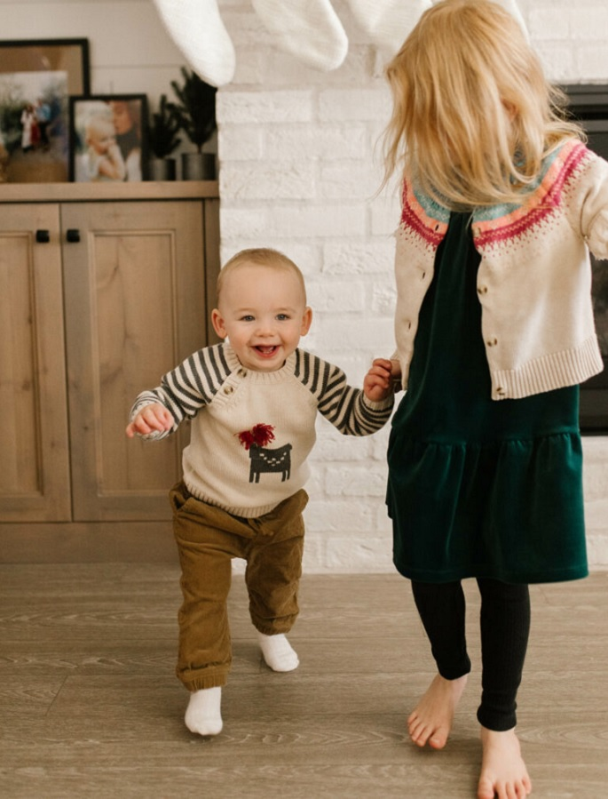 picture of kids wearing warm clothes on a wooden floor in the livingroom