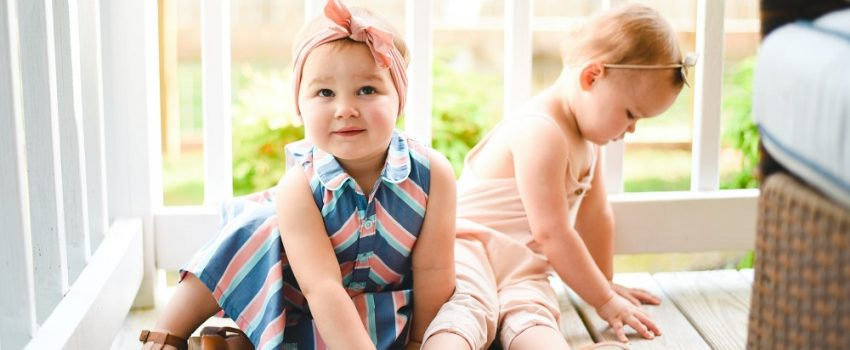 picture of two babies on a porch wearing cute outfits