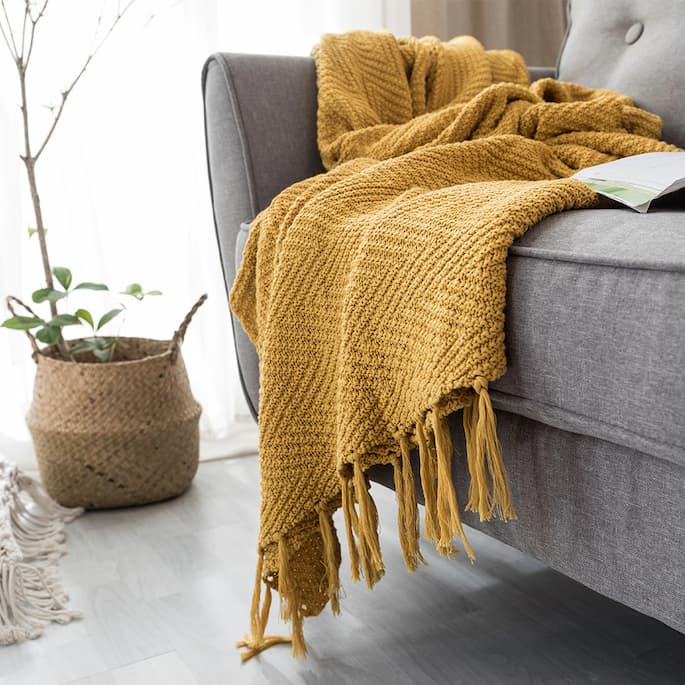 yellow throw blanket on sofa bed