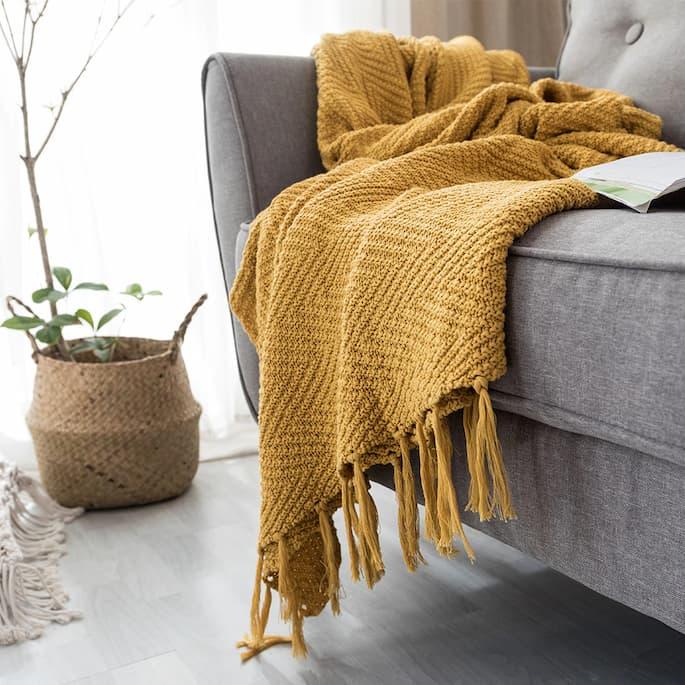 yellow throw blanket on sofa bed