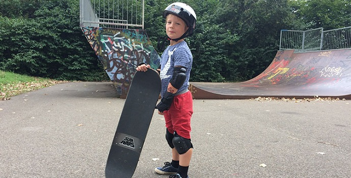 picture of a boy skateboarding with pads and skateboarding gear